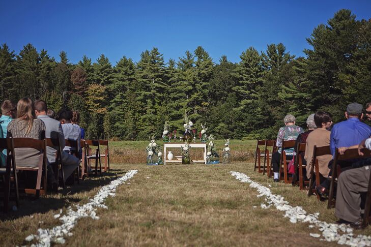 Large glass jugs filled with ivory flowers and dusty miller atop a wooden table provided a backdrop for the outdoor ceremony.