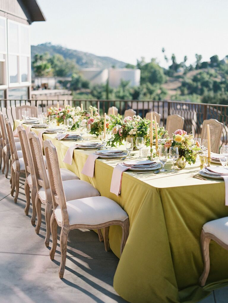 Outdoor summer wedding tablescape with yellow and pink linens and florals