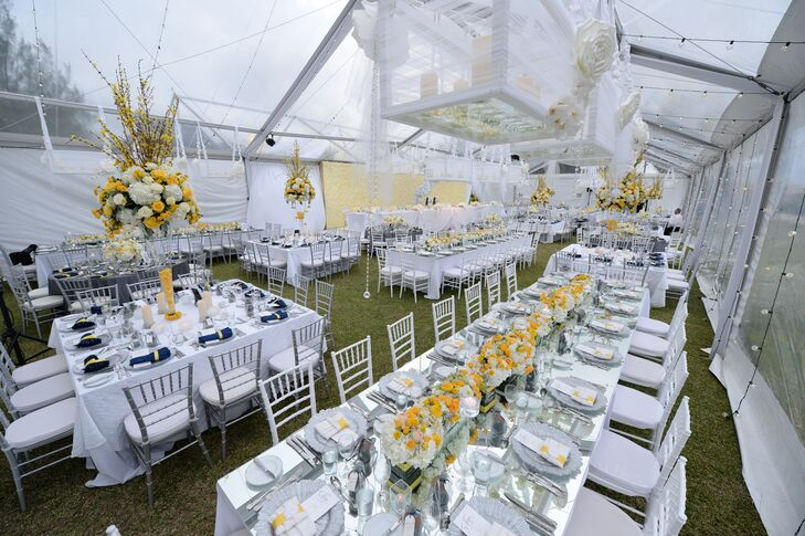 Guests enjoyed a four-course meal inside a transparent wedding tent decorated with yellow and silver details.