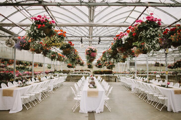 Natural sunlight pouring in from the glass roof lit up the Snow Avenue Greenhouse  in Lowell, Michigan, where the reception took place. Guests sat at long white dining tables set up underneath colorful flower arrangements hanging from the ceiling.
