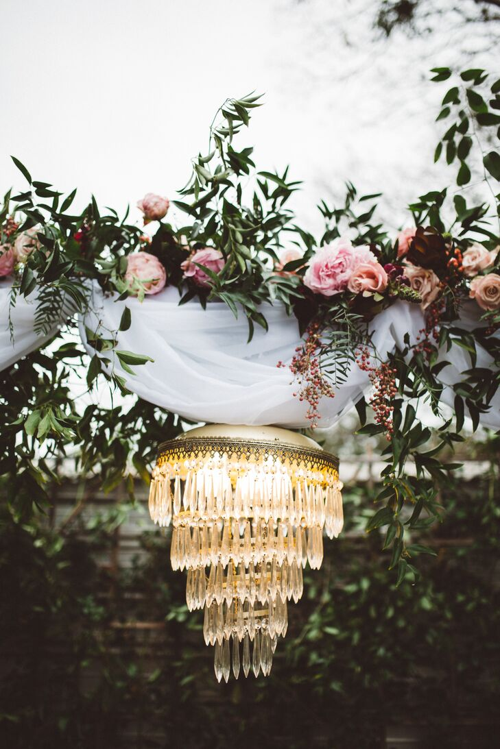 The piece de resistance that brought an element of old-world glamour to Morgan and Stanley's wedding arch was the addition of a tiered crystal chandelier. The luxe lumiere worked with a cluster of ivory pillar candles to cast a warm, ambient glow over the couple as they exchanged vows.