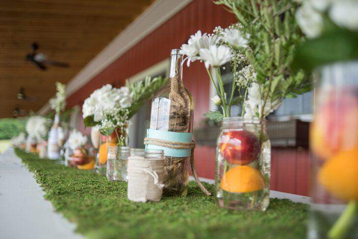 A moss table runner with eclectic vintage jars and vases added to the rustic atmosphere at Buffalo River Farm and Studio Bed and Breakfast in Summertown, Tennessee. White daisies and fresh fruit evoked the University of Tennessee-inspired palette.