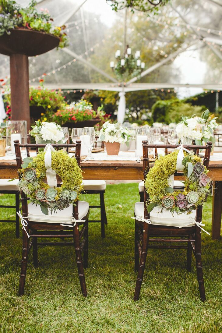 Rustic moss and succulent wreaths hung from the backs of the bride and groom's chairs at the reception.