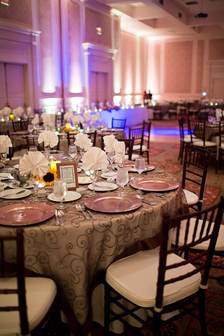 The indoor reception at Founders Inn was illuminated with purple uplighting. The tables were set with embroidered brown linens and chiavari chairs.
