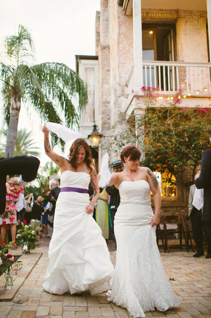 For their wedding, Gretchen wore a strapless trumpet gown with floral lace overlay and a thin beaded belt, while Tyra wore a simple A-line style with a draped bodice and skirt. A purple ribbon tied at the natural waist added a fun pop of color.
