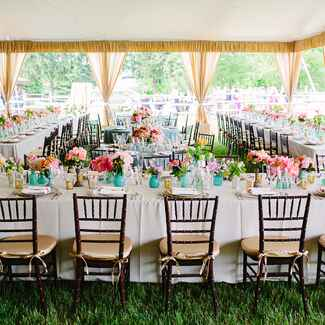 Turquoise and pink tented wedding reception next to barn ceremony