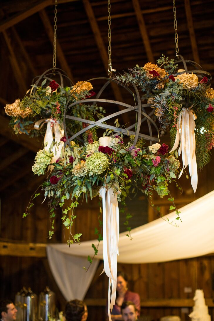 Metal chandeliers hung from the ceiling inside the reception bard, decorated with hydrangeas, dahlias, veronica and an array of several other flowers and greens.
