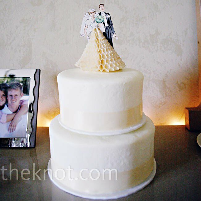 The bride and groom cut into a simple and elegant ivory-colored cake wrapped in matching ribbon and topped with a vintage bride and groom they found on Etsy.com.