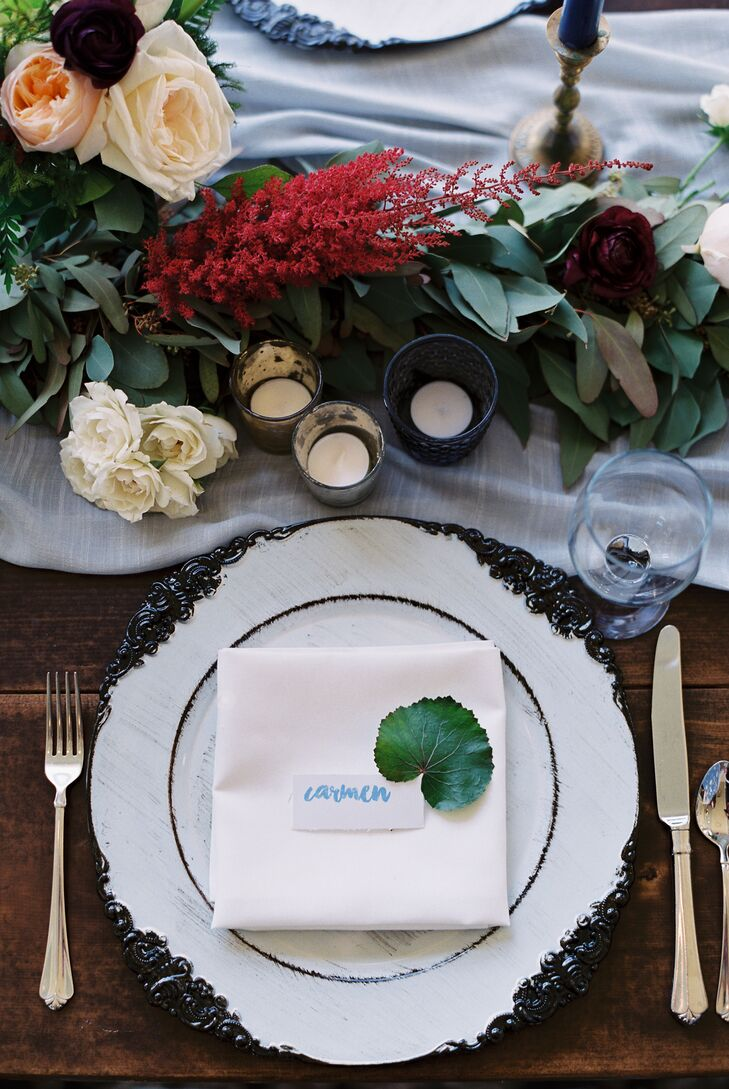 White votive candles and vintage-style ivory plates were accented with centerpieces made with white anemones, dark red ranunculus, black dahlias, peach garden roses and burgundy clematis. They were all set atop a velvet gray runner.