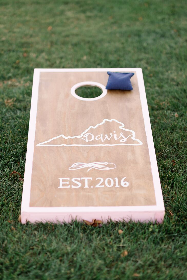 Wedding signs and decorative pieces like the cornhole boards were created by Emma's sorority sister, a talented artist.