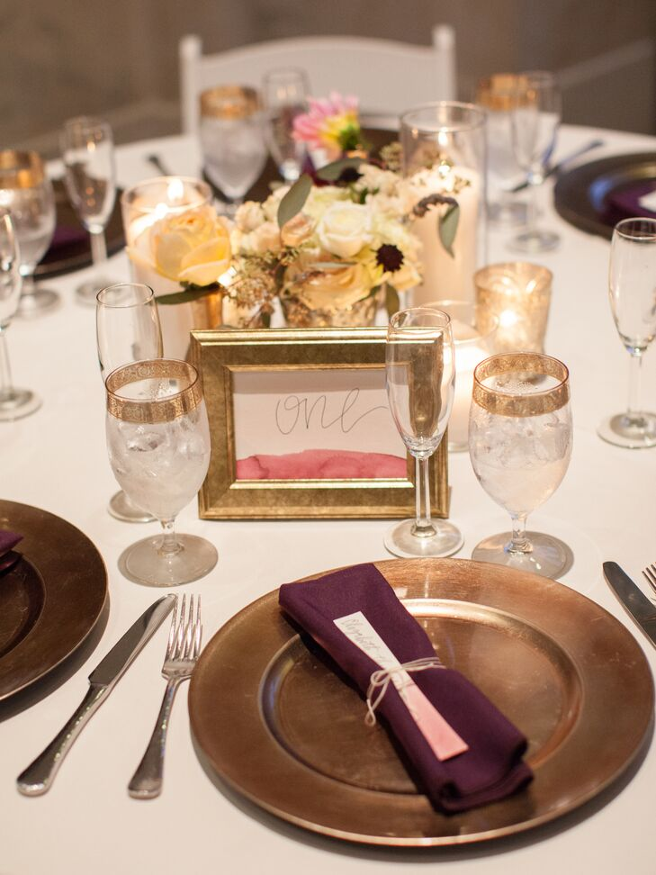 Each place was set with a gold charger, gold-rimmed glass, purple napkin, olive sprig and burgundy and blush watercolor escort card. Framed table numbers were created with watercolor paints and gold calligraphy.