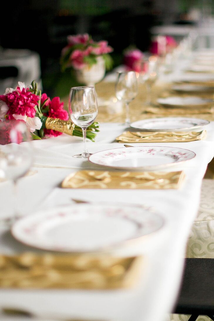 A white tablecloth and delicate white plates allowed the gold napkins and pink flowers to stand out in Anna and Ben's table settings at their reception.