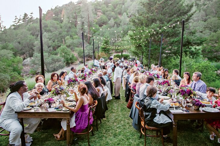 """Market lights were strung over the 12 farm tables, which were left bare for a relaxed touch. """"We let the flower and paper goods make the color statement,"""" Kimberly explains."""