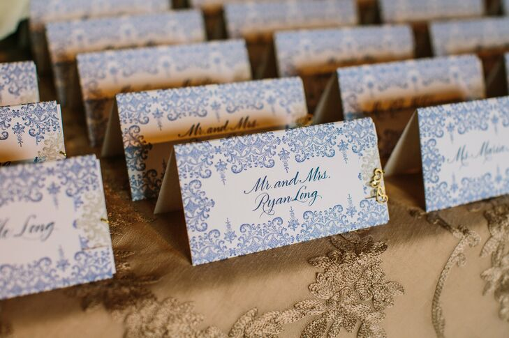 The ornate navy and white tented escort cards featured an interactive element: guests had to pull the decorative gold charm in order to reveal another card with their table assignments.