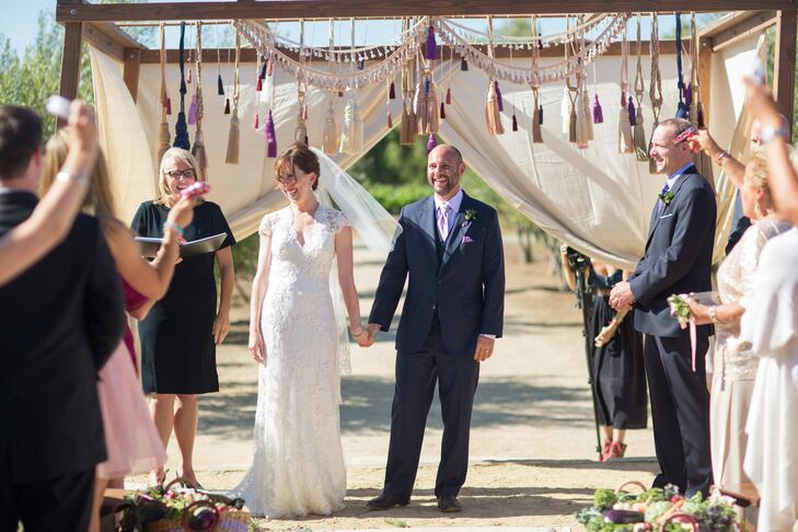 The couple exchanged vows beneath a wooden frame lined with hanging tassels.