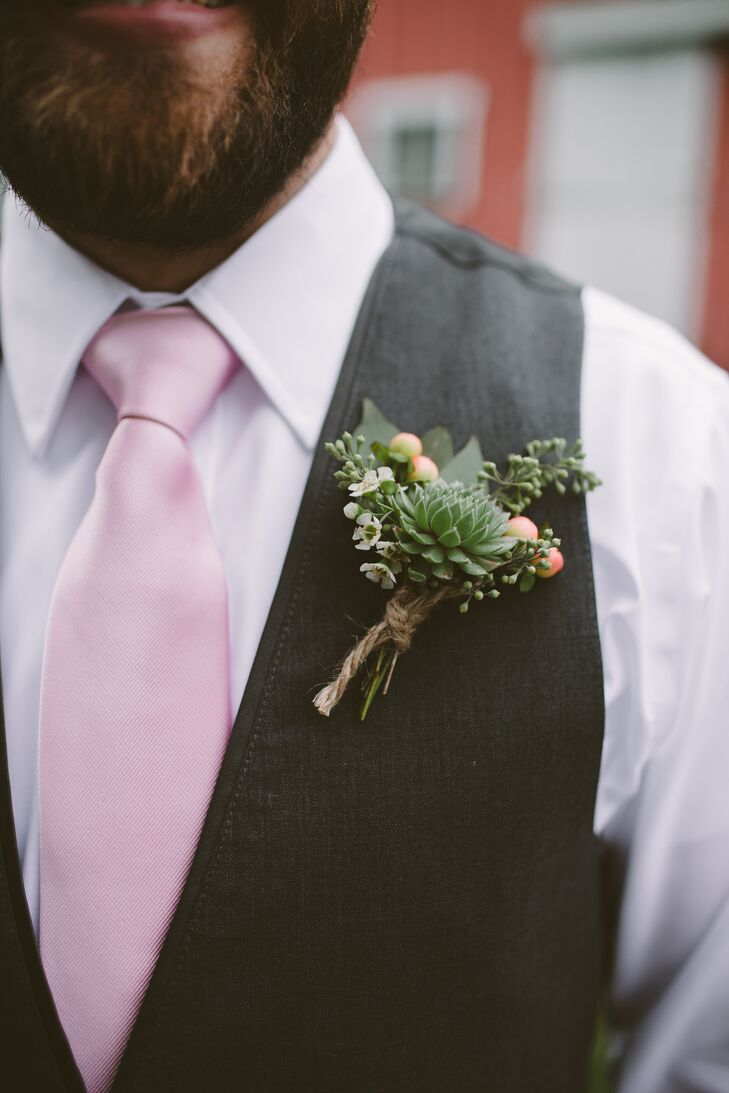 Chris's groomsmen wore boutonnieres made of succulents, hypericum, wax flowers and seeded eucalyptus. They pinned these to their gray vests and wore pink ties for a pop of color.