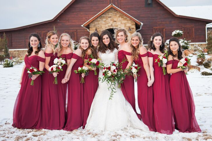The bridesmaids were dressed in glamorous floor-length, bourdeaux off-the-shoulder dresses. Each carried a similar bouquet to the bride full of roses, greenery and pivot berries.