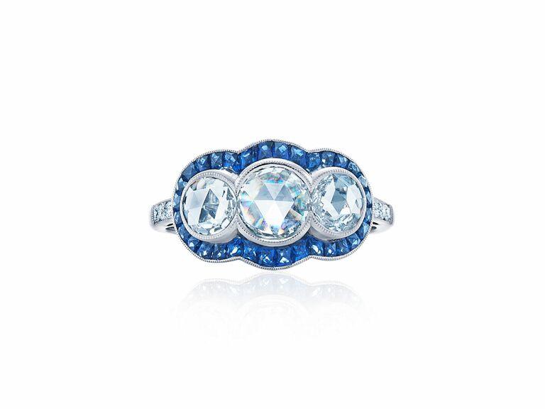 Three rose cut round diamonds and a sapphire halo in platinum