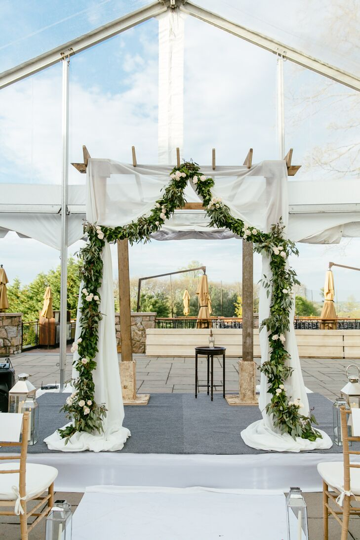 Inspired by a photo Jenna saw on Pinterest, their wedding arbor perfectly captured the theme. Sheer white fabric draped over the exposed wood while a garland of seeded eucalyptus and white roses covered the front.