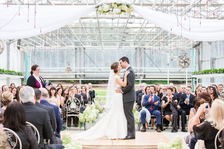 The ceremony took place in the afternoon inside the farm's expansive greenhouse overlooking the surrounding fields in Lexington, Massachusetts. Bushel crates filled with limelight hydrangeas and white pumpkins greeted guests as they arrived, and galvanized pails overflowing with the farm-fresh blooms lined the aisles. A platform was built in the center of the room, upon which the couple exchanged vows, surrounded by their families and friends, with airy panels of sheer white fabric and bundles of limelight hydrangeas hanging overhead. After the ceremony guests were invited into the field to enjoy a glass of prosecco and johnnycakes with relish made with Wilson's Farms beautiful beets.