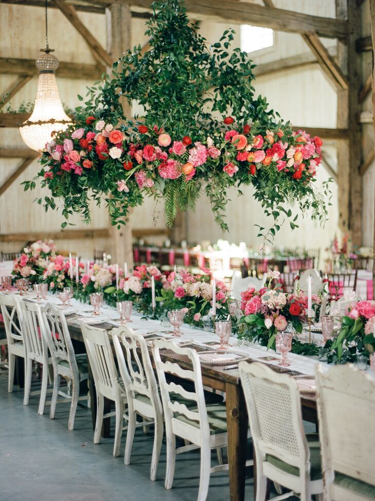 A luscious six-foot flower chandelier hung over the banquet table at the barn reception at Chandelier Grove in Tomball, Texas. It was crafted with peonies, garden roses and lots of greenery.