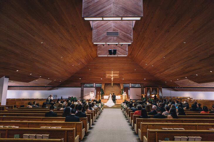 The couple married at Our Lady of Grace church in El Cajon, California. To brighten up the wood interior, the couple strung each pew with a cascading floral garland and gold bow.