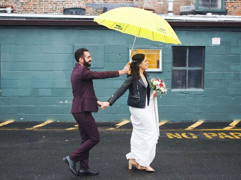 stylish bride and groom walking with yellow umbrella