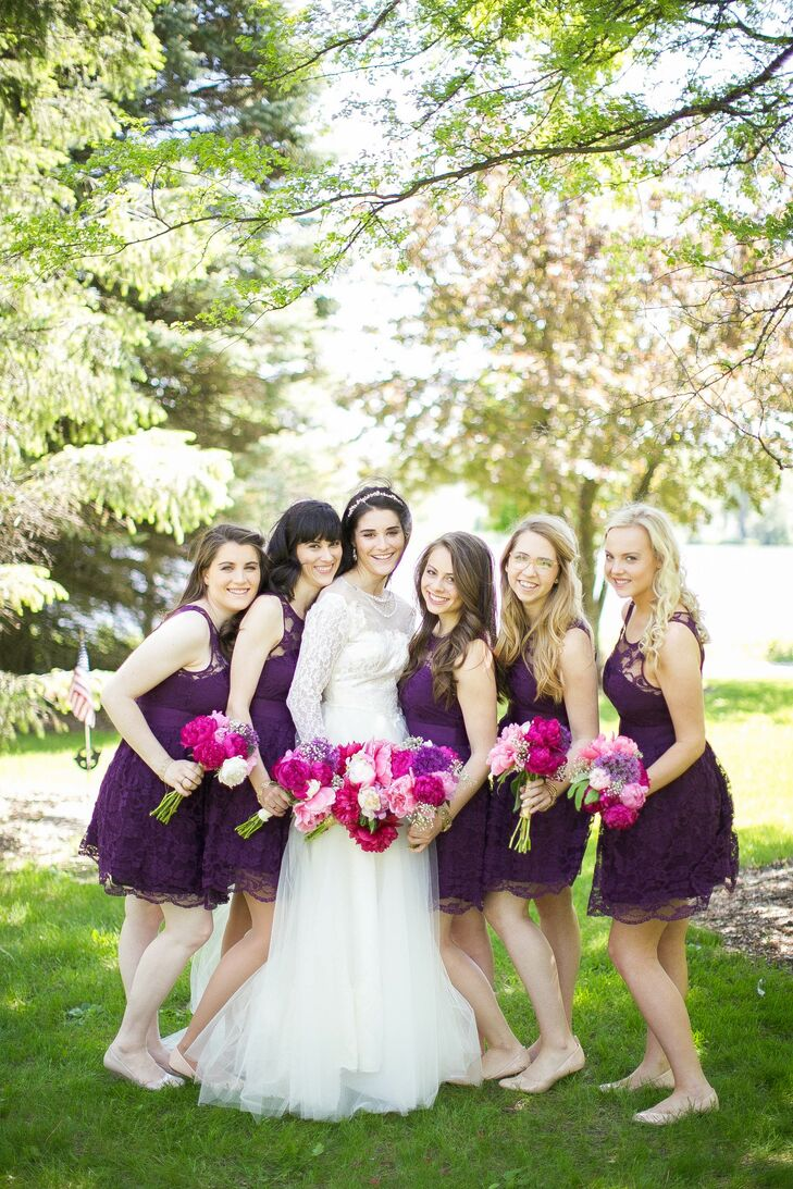 To match the relaxed vibe of the ceremony and reception, Anna's bridesmaids wore plum-colored knee-length dresses from ModCloth. The lace overlays matched Anna's gown, while the plum color matched the flowers and decor at the reception.
