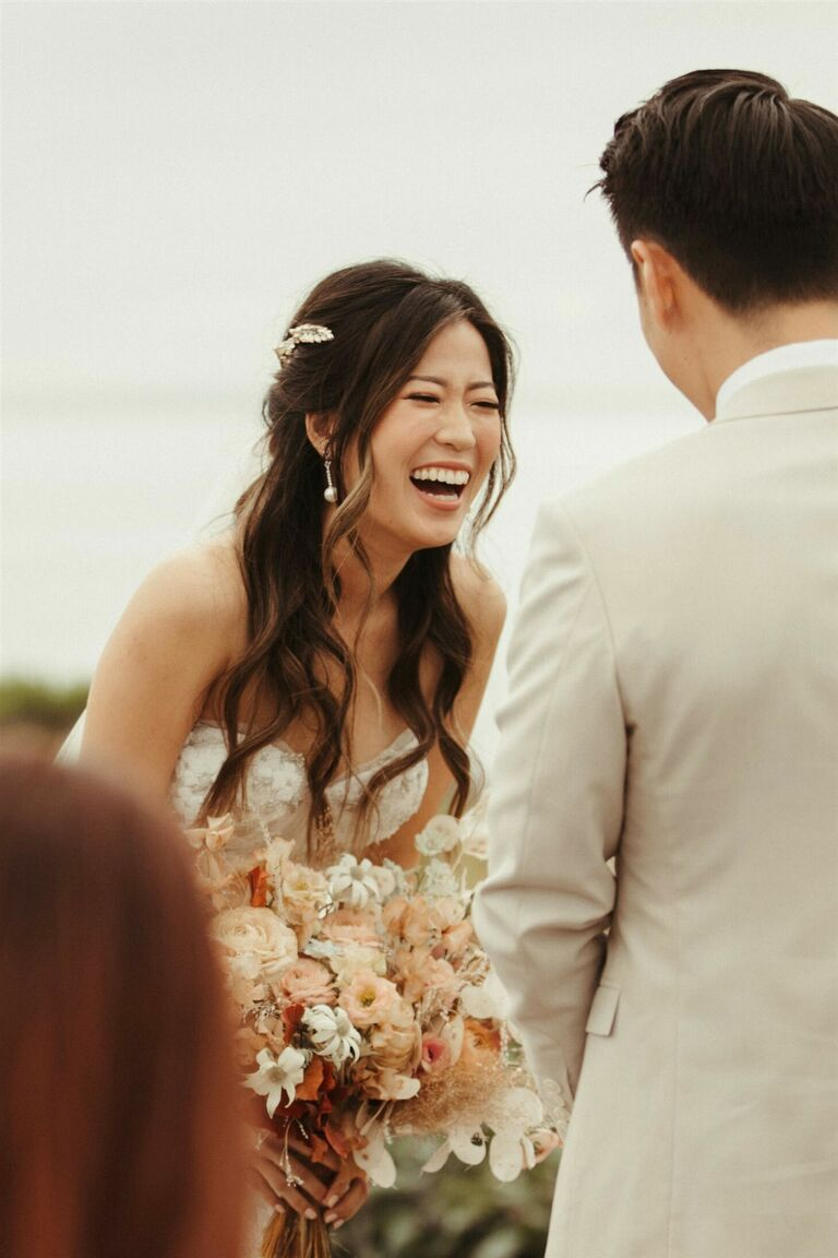Bride with beauty waves laughing during vow exchange