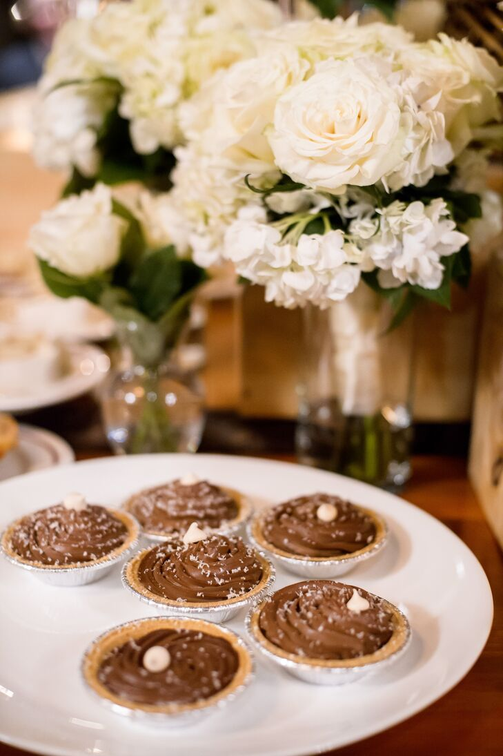 Guests enjoyed a doughnut cake after dinner. As a nod to Pi Day (the wedding was on March 18), Erica and Janson served a selection of mini pies. Guests also made s'mores by the fire pits as snow fell gently over the scene.