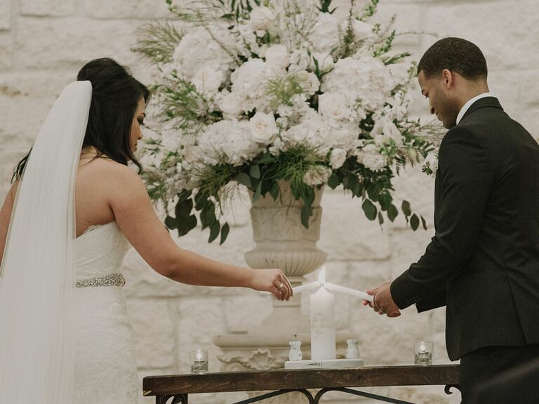 Bride and groom lighting candle during wedding unity ceremony