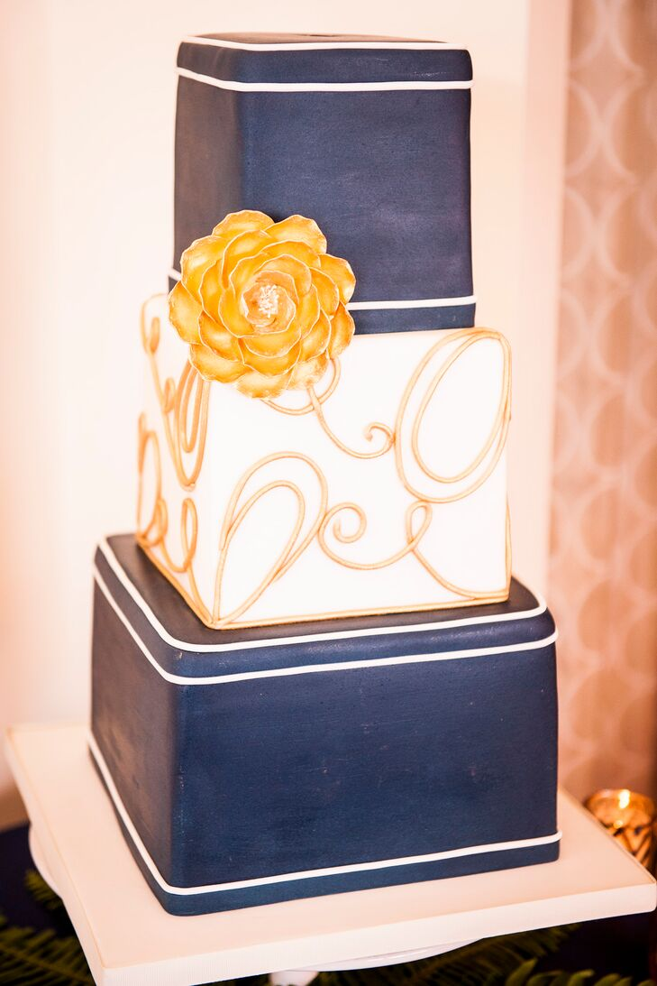 The top and bottom tier of the wedding cake was covered in navy, and the middle tear was white with swirls of gold. A single gold cake flower decorated the side of the cake.