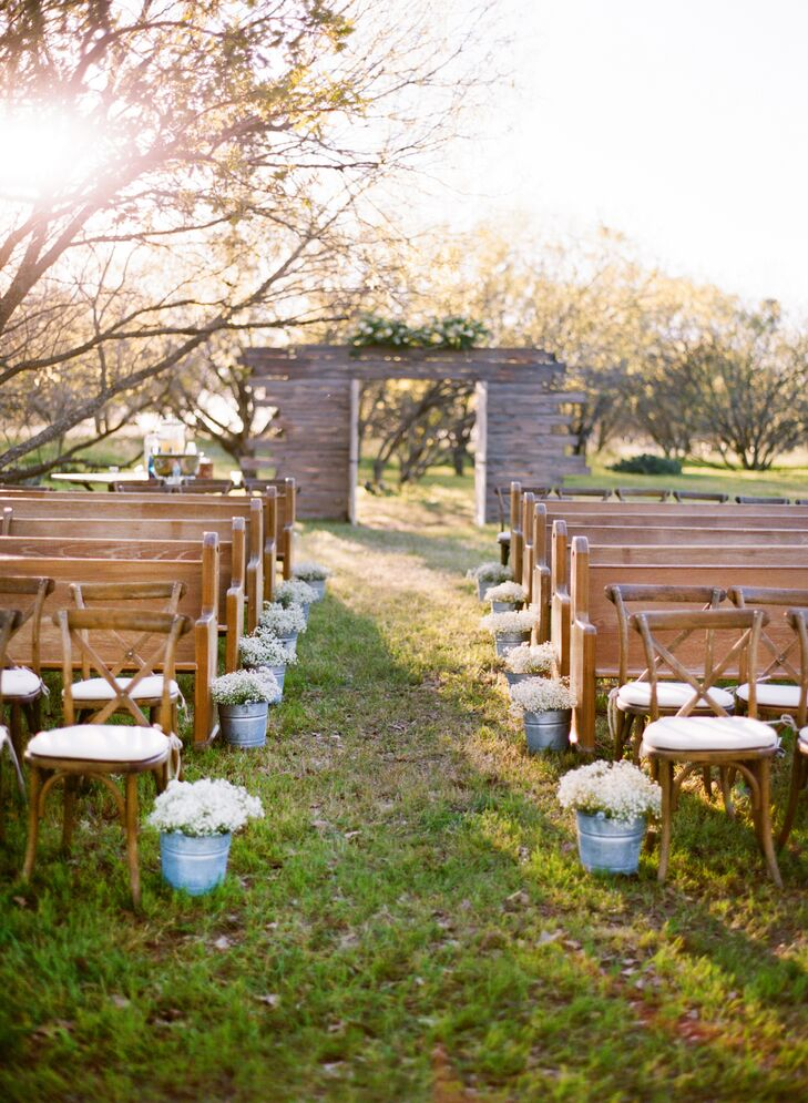 White flowers like baby's breath were used in the aisle, set inside galvanized pails as well as the tall upright amaranthus arrangements used in the reception. Florals were chosen to accent the natural Texas scenery.