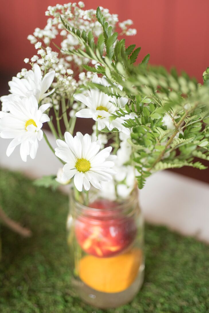 White daisies and baby's breath in mason jars brought a laid-back and Southern feel to the reception at Buffalo River Farm and Studio Bed and Breakfast in Summertown, Tennessee. The mason jars also had fresh peaches and oranges to bring out the palette.