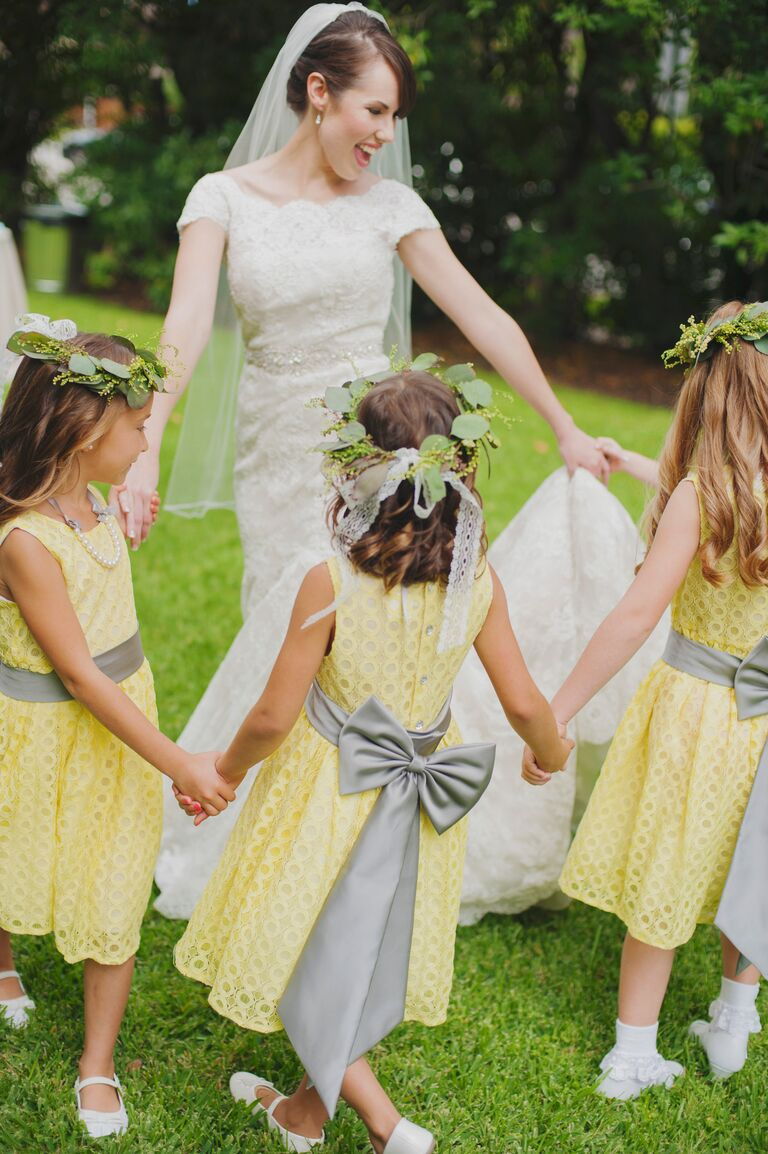 Bride in fingertip-length veil dancing with flower girls