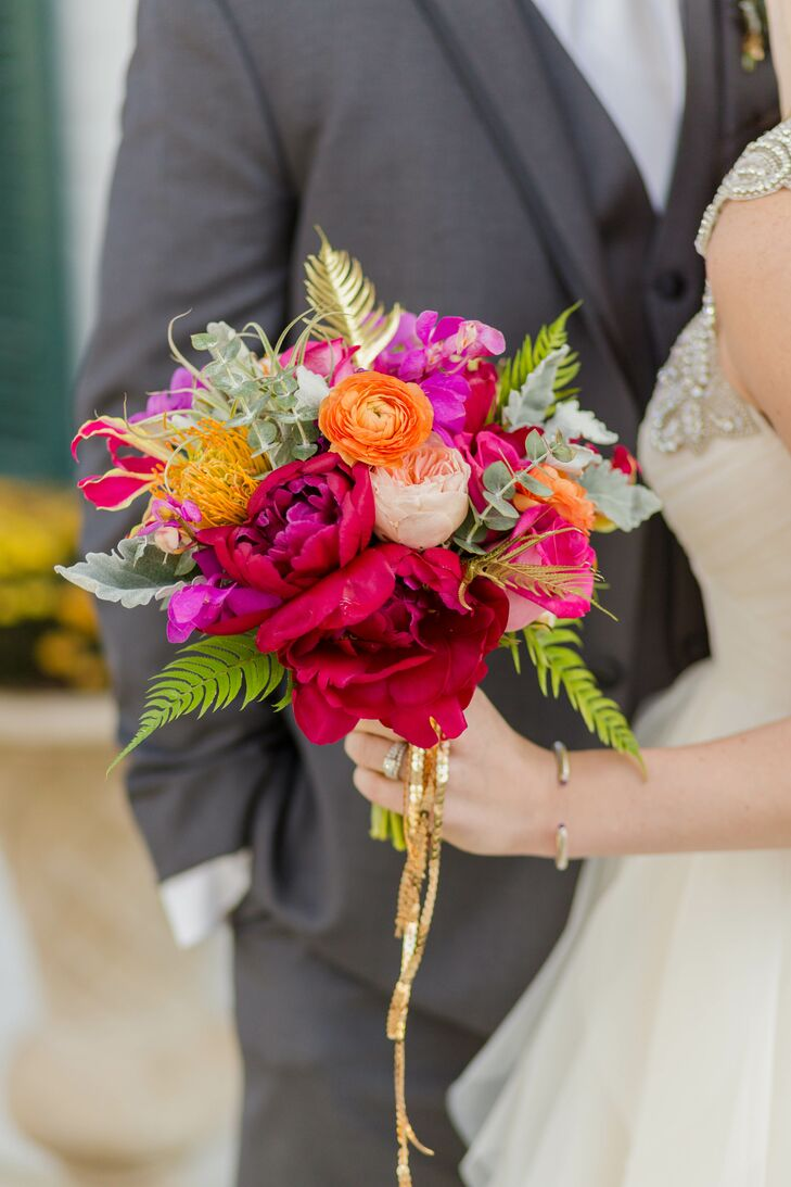 Chelsea carried pink peonies, orange ranunculus, blush garden roses, yellow protea and mint lamb's ear in her lush, colorful bouquet. Her florist and planner Sarah Lambert from Soirees and Bouquets, also dipped some fern leaves into gold paint to add a little sparkle to the bouquets. She completed the look by wrapping the stems in a gold sequined ribbon.