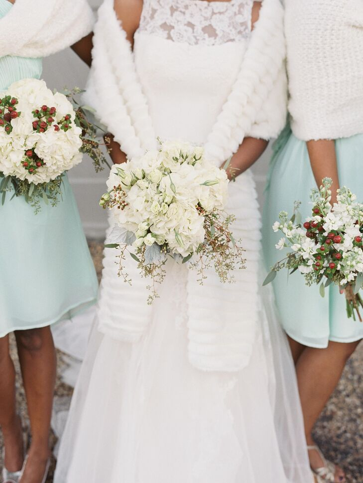 Alexandria carried a white bouquet with hydrangeas, lisianthus, roses, wax flowers, seeded eucalyptus and lamb's ear. Her bridesmaids carried white bouquets with one variety of flower from Alexandria's bouquet and red hypercium berries.