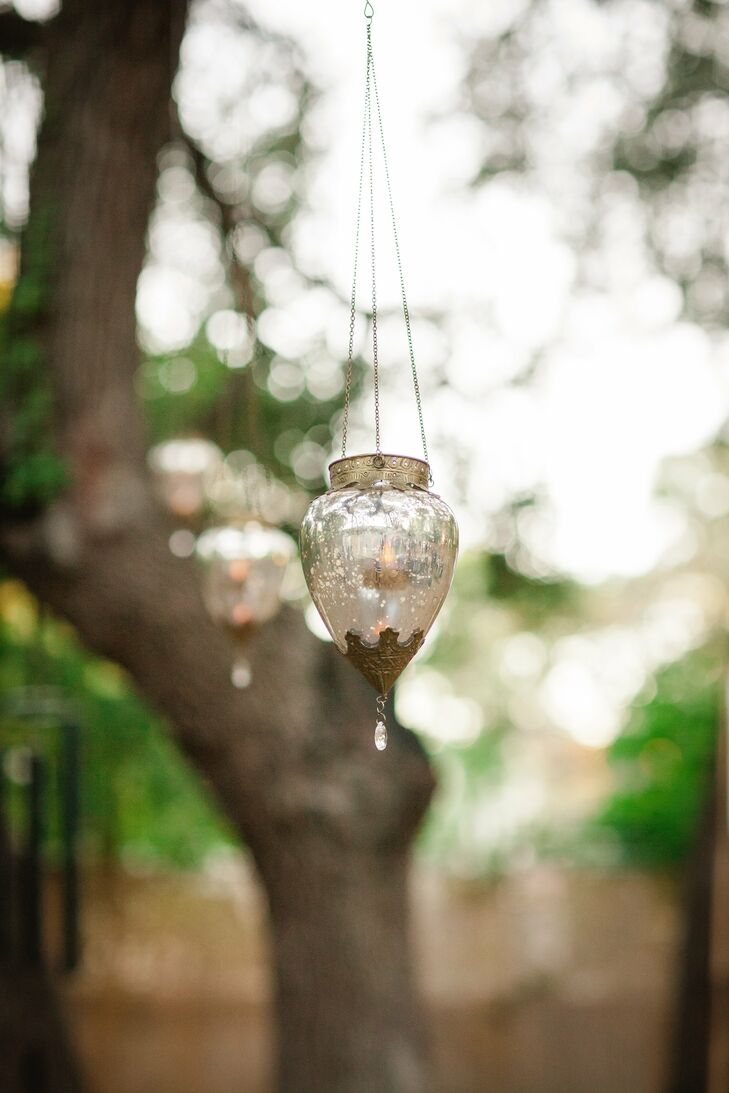 Vintage mercury glass lanterns were hung from the trees to give the ceremony a whimsical vibe.