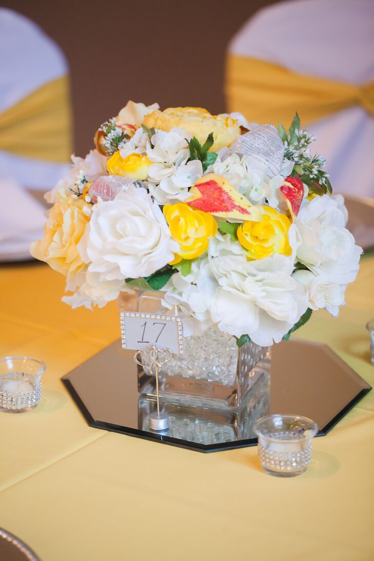 Dining tables had centerpieces filled with a range of colorful blooms, from roses to peonies and hydrangeas, at the reception at Asbury Park Grove in Charlotte, North Carolina. The centerpieces sat on top of flat octagon-shaped mirrors.