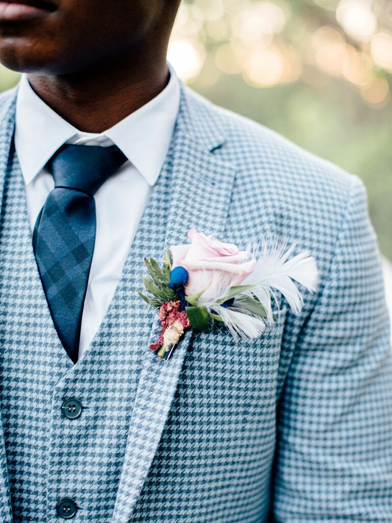 Groom wearing pastel pink floral boutonniere and blue houndstooth suit
