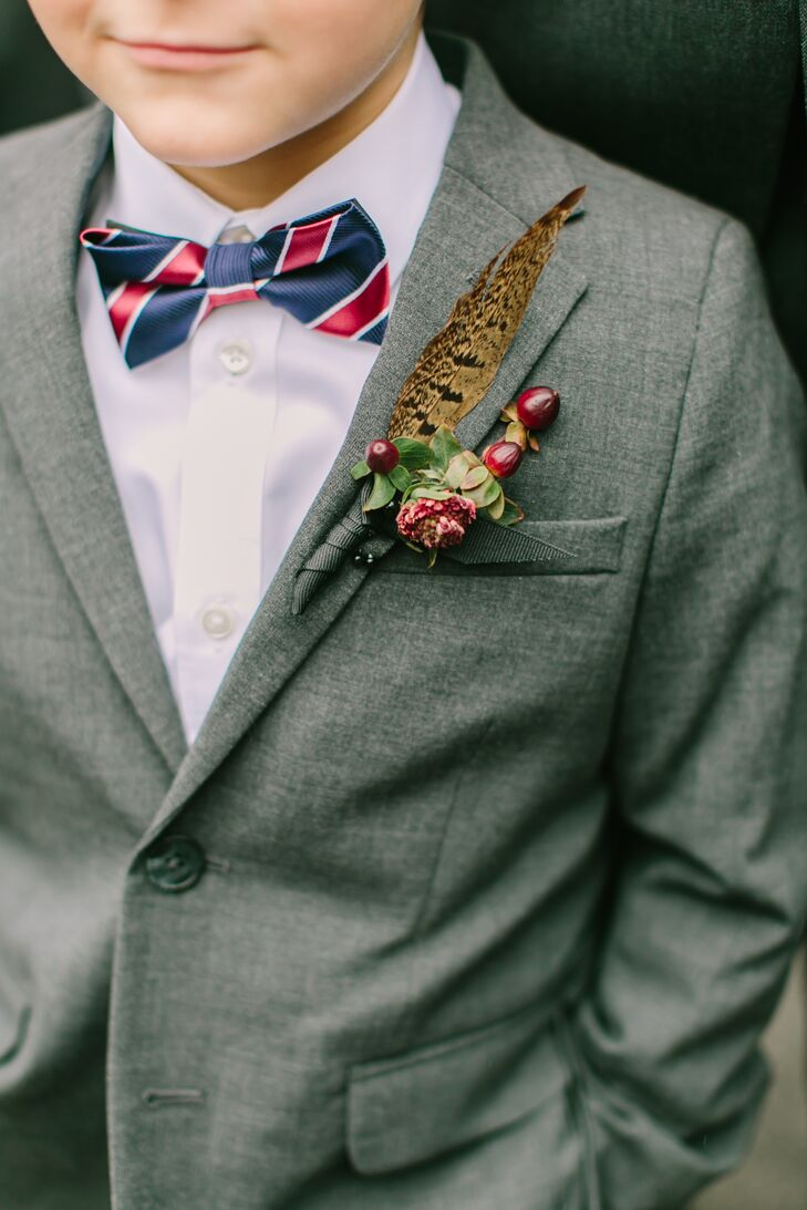 The couple's planner paid tribute to Christopher's love of pheasant hunting by incorporating pheasant feathers into the boutonnieres. For a touch of seasonal flair, she teamed them with burgundy hypericum berries that popped against the wedding party's gray suits.