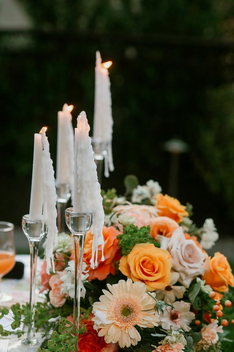 Orange centerpiece with roses and daisies accented by taper candles