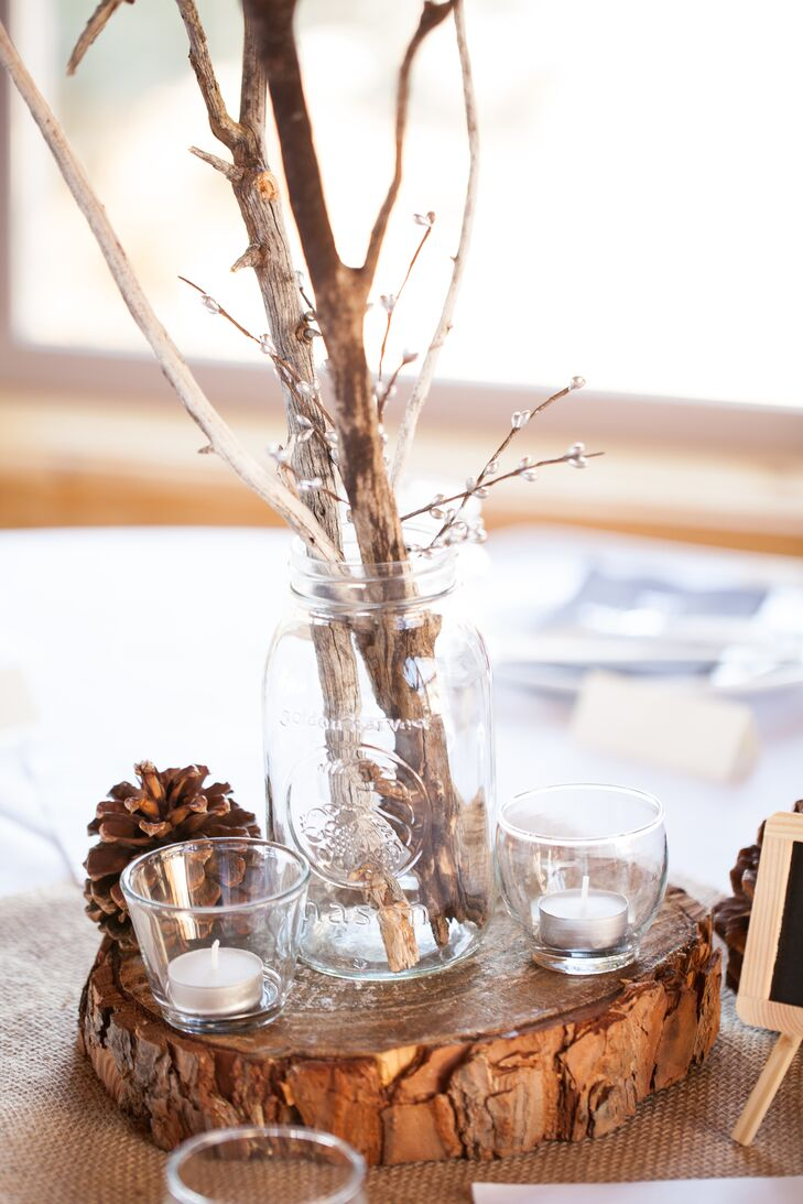 The reception took place in the downstairs area of the rented house, where glass mason jars filled with branches decorated dining table surfaces, surrounded by pinecones and candles.