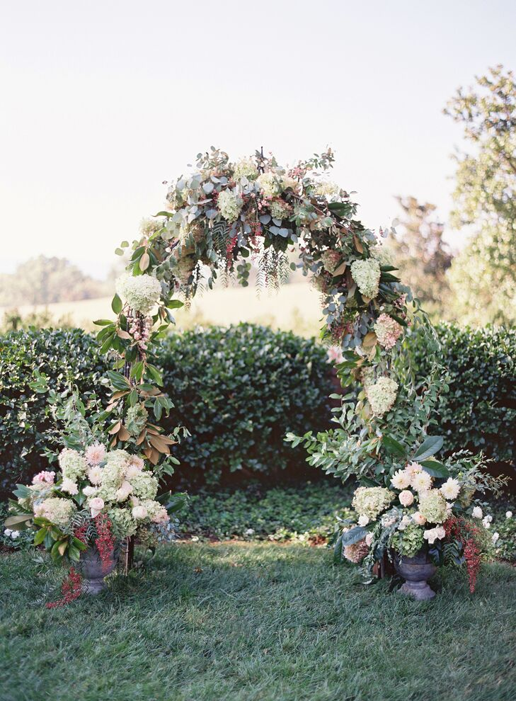 Overflowing arrangements of hydrangeas, greenery and hypericum berries in rustic urns marked the beginning and end of the ceremony aisle.