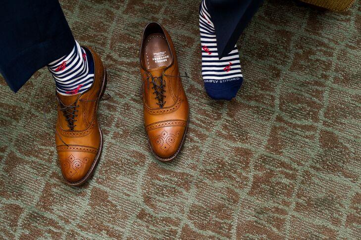 The groom accessorized his navy blue suit with nautical accents like a colorful Vineyard Vines tie and blue and white socks with lobster embroidery,  to play up the feel of the Nauticus Marina, where the bride and groom had their reception.