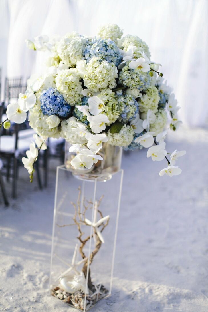 The ceremony aisle was decorated with lush floral arrangements containing blue and white hydrangeas, orchids and roses with starfish, driftwood and sea shell accents.