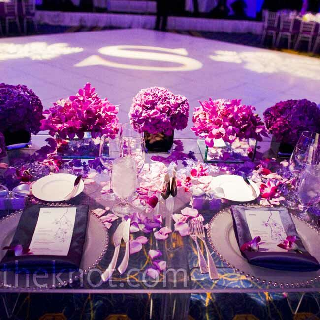 Rose petals and low, purple arrangements covered the couple's Lucite sweetheart table. Nicole loved that guests could still see her gown through the clear tabletop.