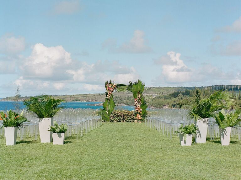 Outdoor tropical wedding with potted palm leaves and tropical flowers