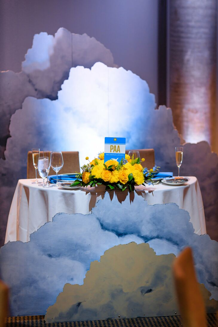 Whimsical Sweetheart Table with Cloud Decorations and Yellow Flower Centerpieces