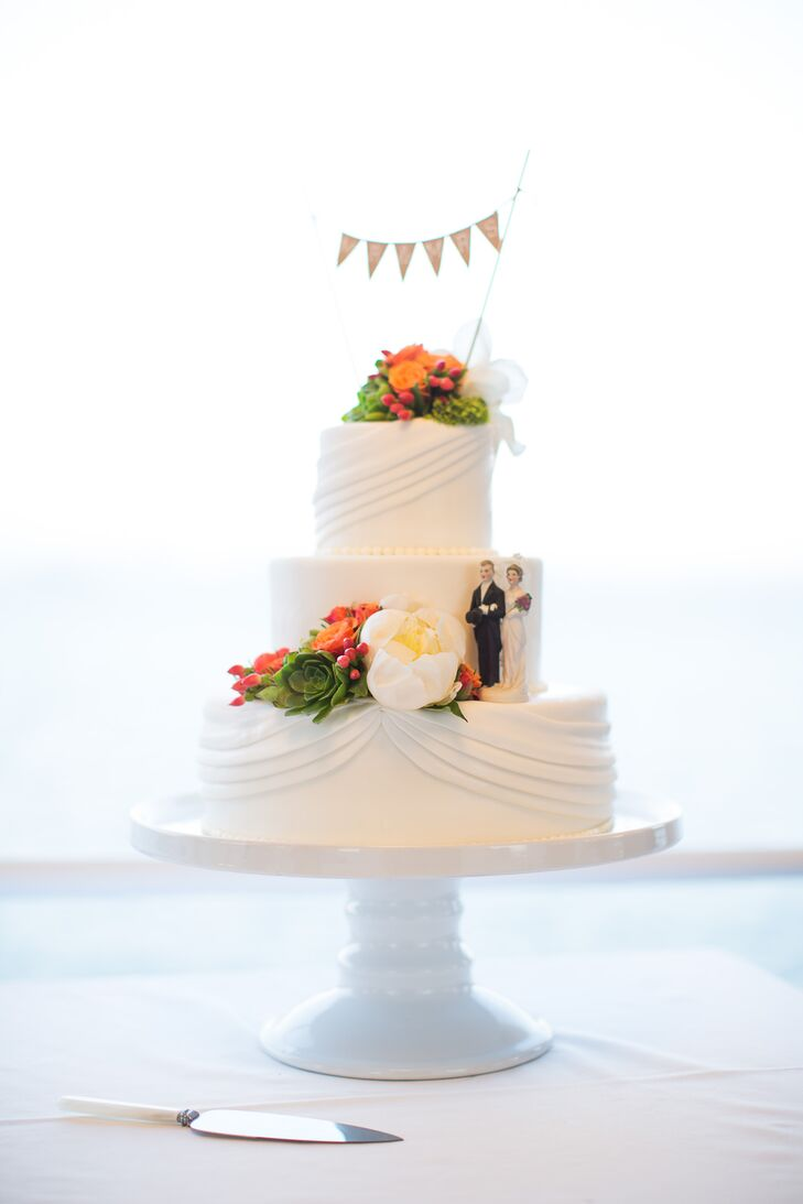 The three-tier white cake sat on top of a simple white stand, displaying the delicious-looking dessert for all to admire. White and orange blooms accented the surface of the cake with a draping design, topped with a burlap flag decoration.